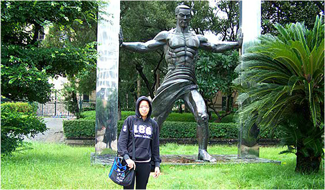 Bag and friend (looking perplexed) in front of a statue paying tribute to the physical prowess of the Chinese, Shenzhen, China, June 2012
