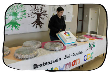 TC Newman CDC staff member admiring the winner's cake and snacks.
